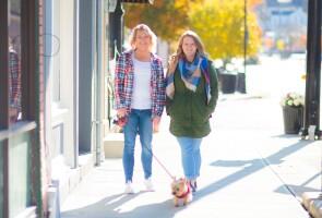 Sonya Fox and Rebecca Moore walking a dog on the sidewalk