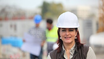 A photo of a woman wearing a hard hat at a job site