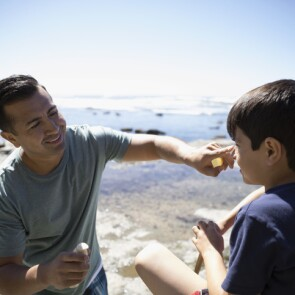 A father applying sunscreen to his son's face at the beach