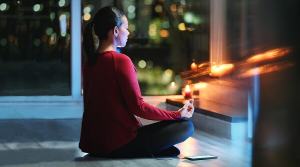 Woman with dark hair in a ponytail wearing a red shirt meditating