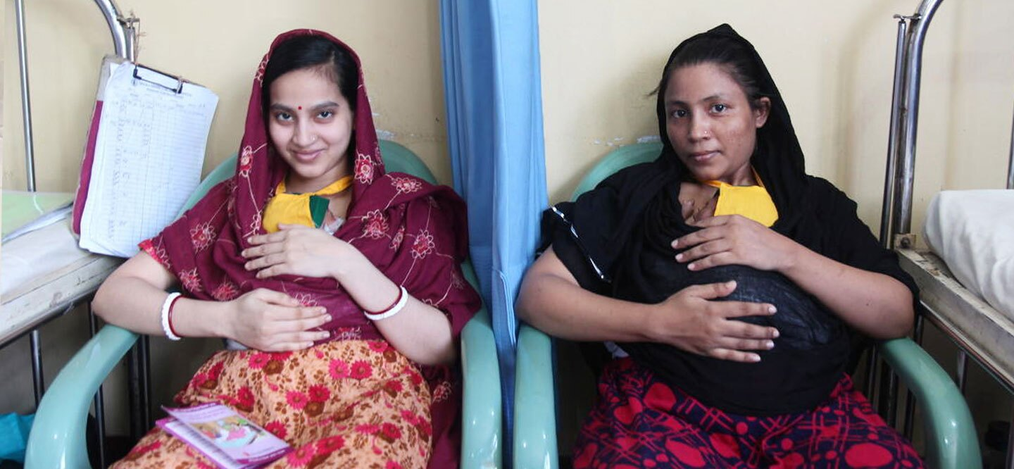 Two mothers in Bangladesh neonatal intensive care unit practicing kangaroo mother care