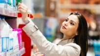 woman in raincoat looks at products on a supermarket shelf