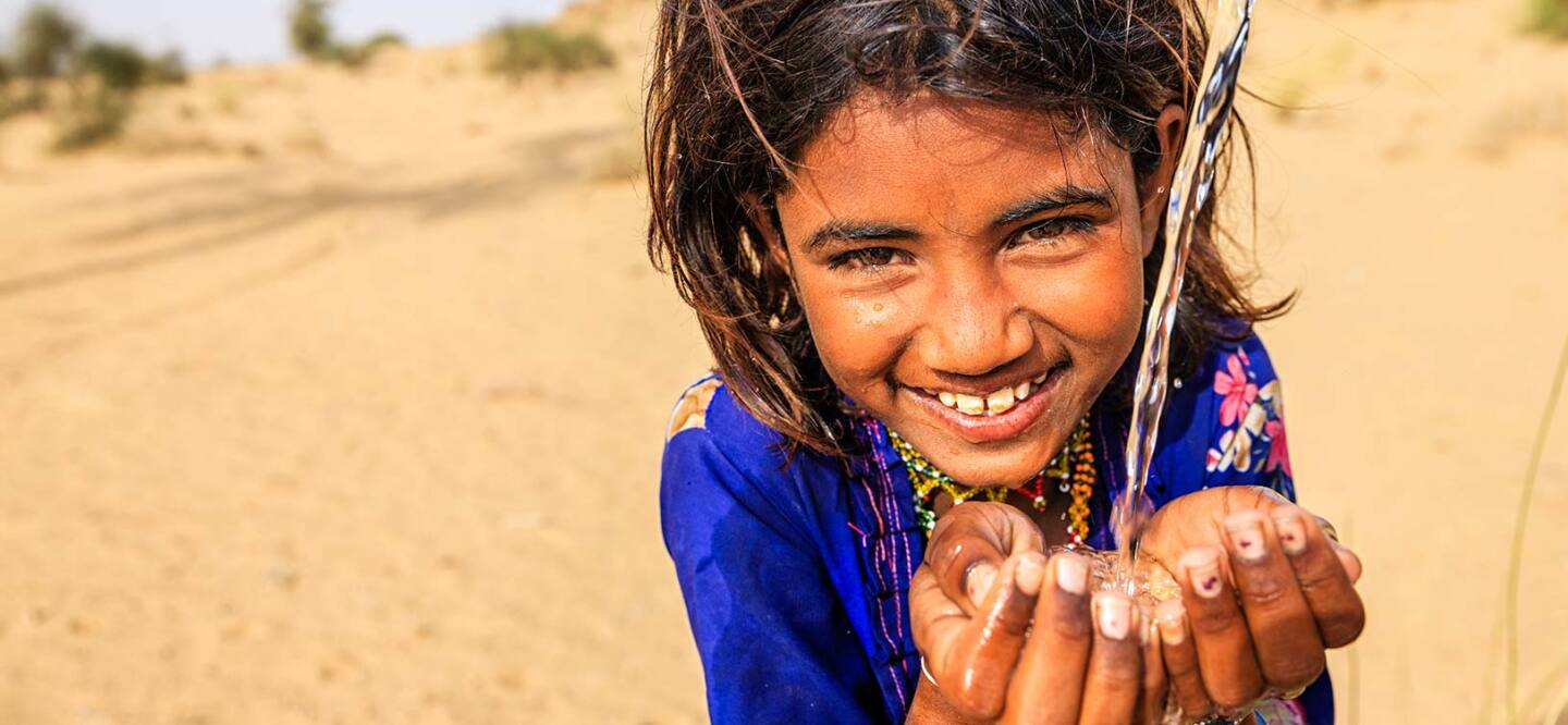 A photo of a girl drinking water from her hands