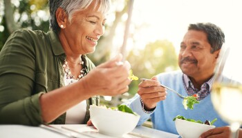 A photo of two people eating salads and smiling