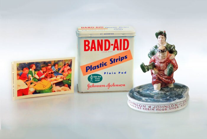 "Special tins of ""Sherwood Green"" BAND-AID? Brand adhesive bandages, an Adventures of Robin Hood trading card, and a collectible figurine"