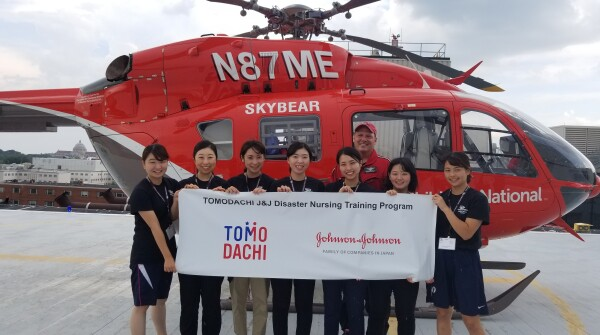 The Tomodachi J&J Disaster Nursing Training Program class of 2018 posing in front of the Children's National Health System helicopter, which transports sick patients.