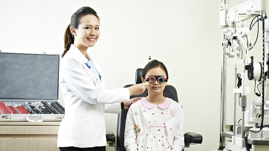 An optometrist at the Singapore National Eye Center performing a vision exam on a young girl