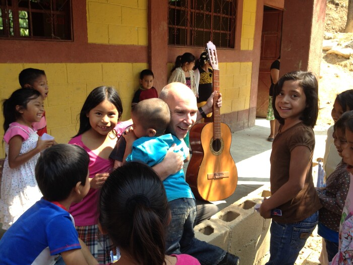 A photo of Reinhard Juraschek with children and a guitar in Guatemala