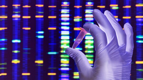 Hand holding vial in front of DNA graphic
