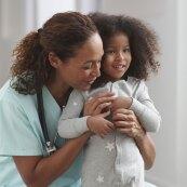 A photo of a nurse hugging a girl