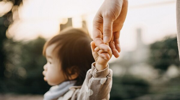 Parent holding their toddler's hand