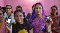 Indian women hold up their cell phones