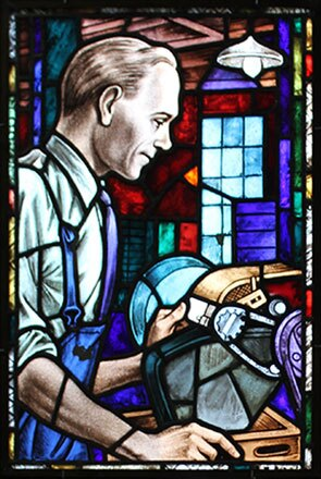 A stained glass window portrait showing a former Johnson & Johnson employee using a material-shaping tool