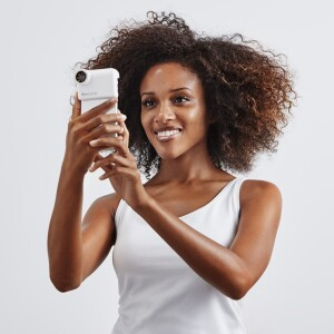 Woman holding iPhone with a Neutrogena Skin360 skin scanner attached