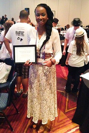 Attractive feminine-presenting person, standing tall, proud, happy, Alisha Bridges, psoriasis advocate, holding Psoriasis Innovator award indoors at convention.