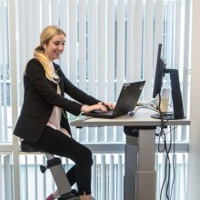 A photo of an employee using a bicycle desk while on her laptop at the Johnson & Johnson office in Irvine, California