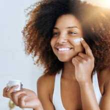 A photo of a woman applying face cream to her cheek