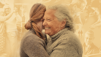 An older woman hugging a younger woman in front of a collage of photos