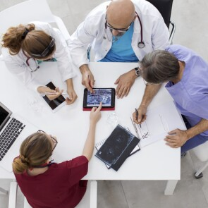 Doctors sitting around a table with tablets