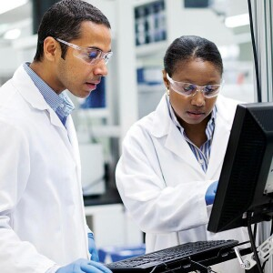 Two researchers looking at a computer screen in a lab