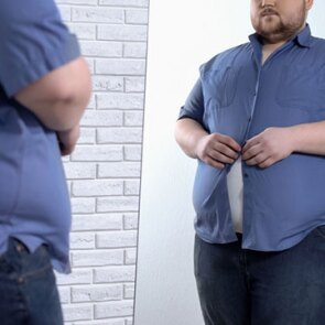 Image of man standing in front of a mirror buttoning a too tight shirt