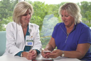 Patient Michele Paul using the Johnson & Johnson Health Partner app with a nurse