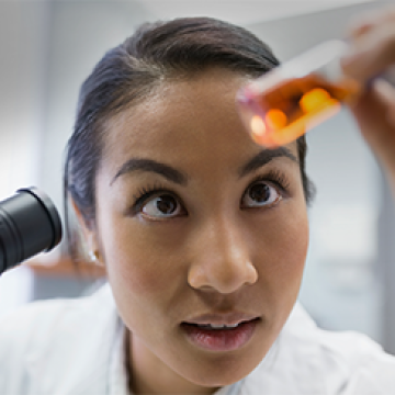A photo of a scientist looking at a vial