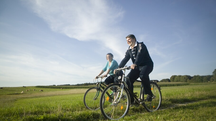 A photo of a man and woman bicycling in a field of grass