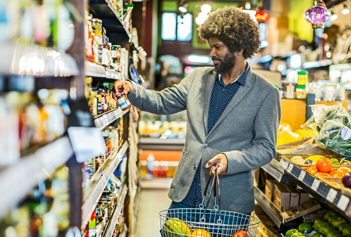 Man in a blazer shopping for supplements at a grocery store with a basket full of fruit