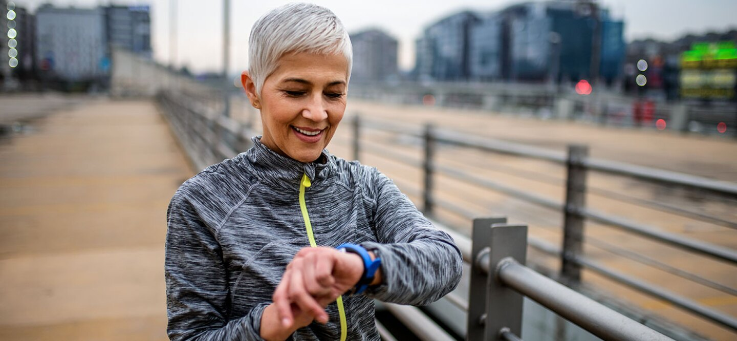 Silver-haired woman exercising looking at her fitness watch.