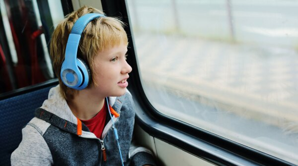 A photo of a boy wearing blue headphones and looking out train window
