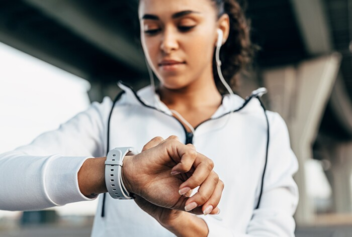 Woman checking her smart watch while exercising.