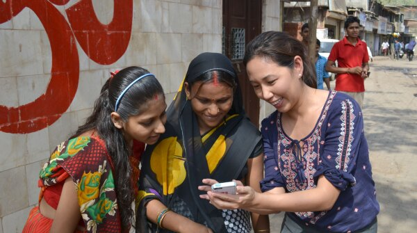 A photo of Alice Lin Fabiano showing mMitra on a cell phone to two mothers in India