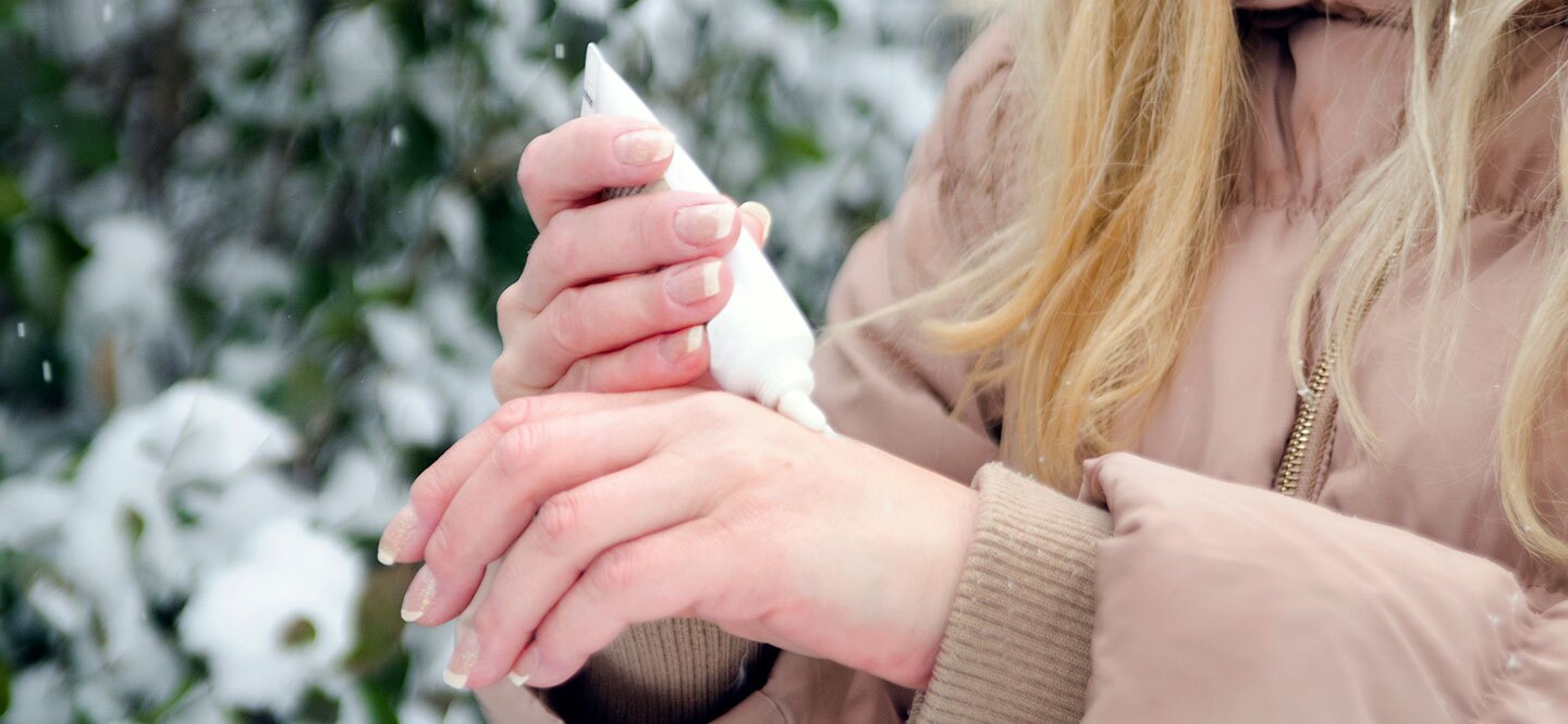 Woman applying lotion to her hands in the winter