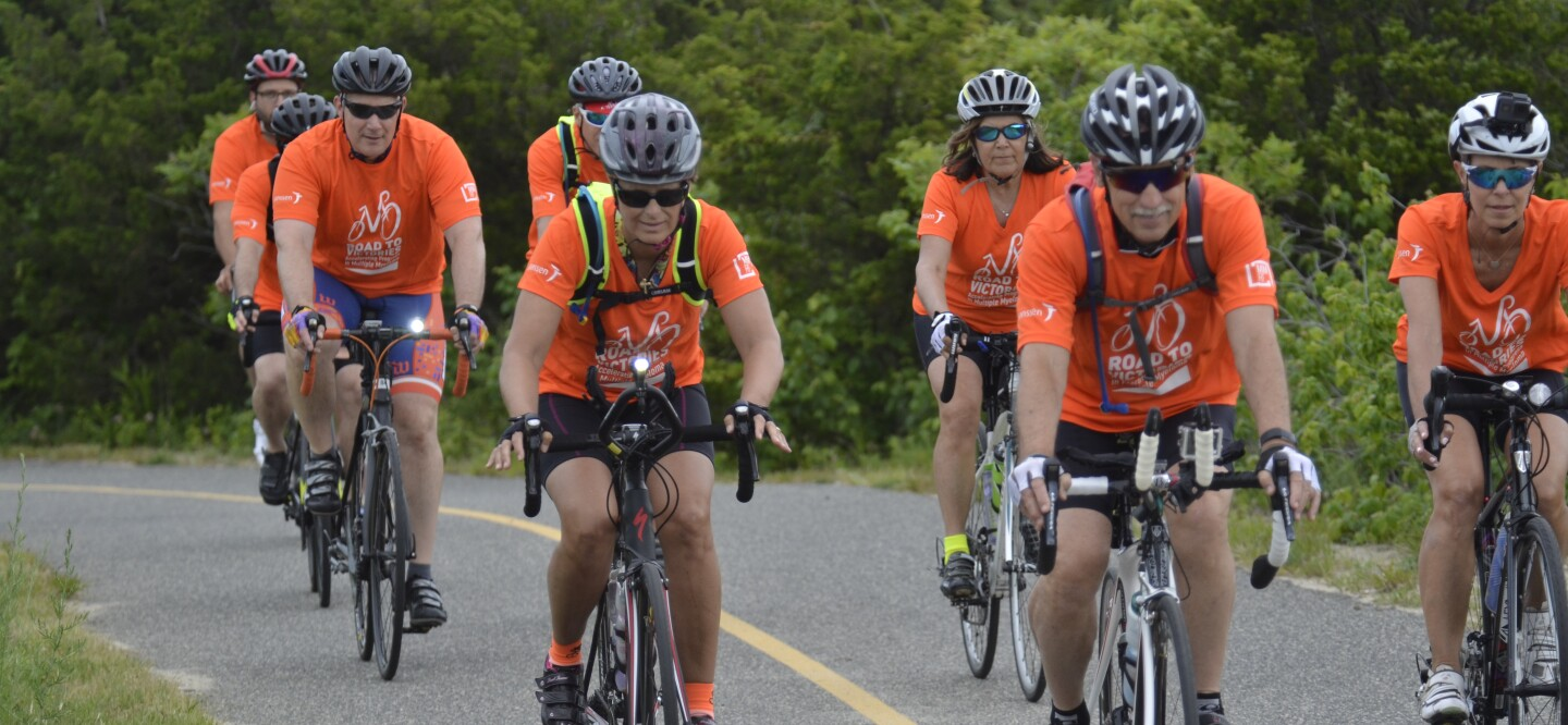 A photo of Carmen and Mike with Road to Victories participants on a training ride