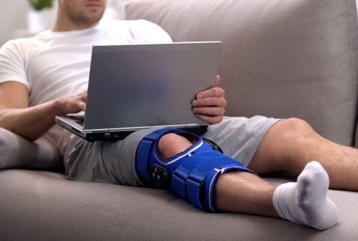 Man in knee brace looks at laptop
