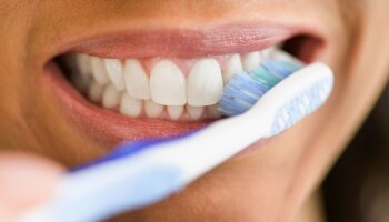 A close-up of a woman brushing her teeth