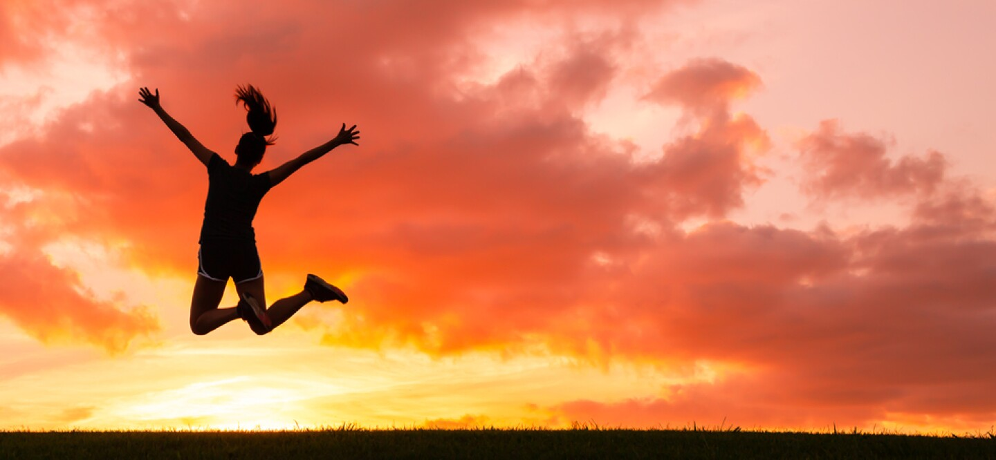 A photo of a woman jumping in front of a vibrant sunset