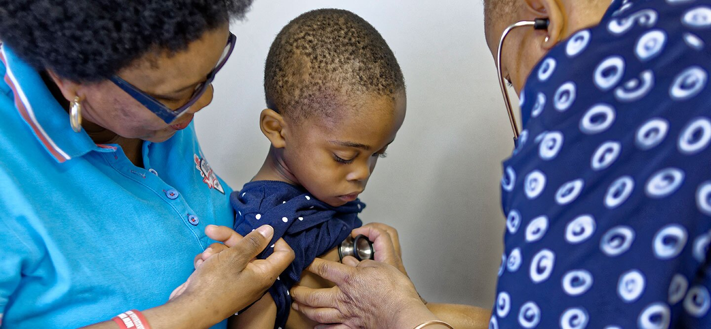 A healthcare provider uses a stethoscope to listen to a young boy's chest.
