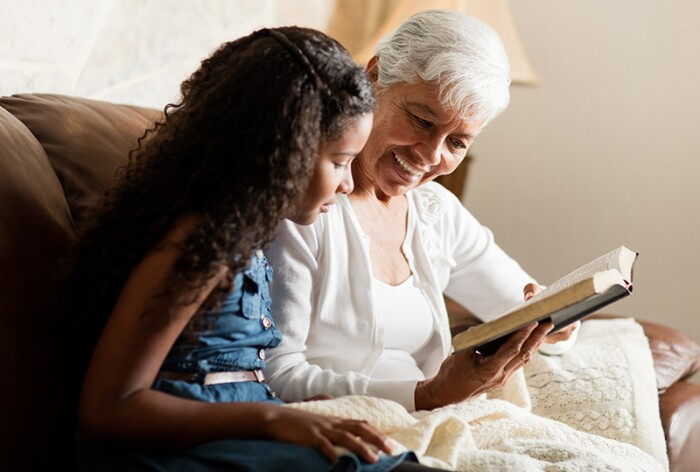 Older woman reading with a younger girl