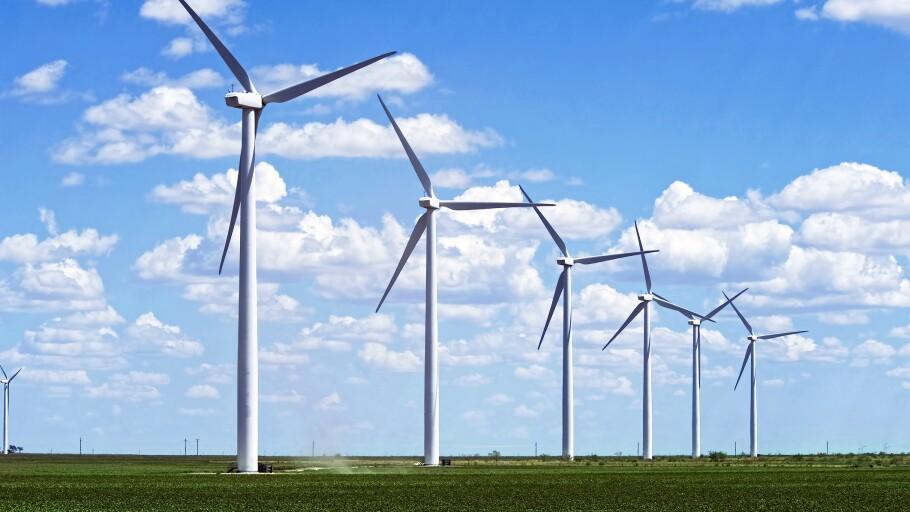 A photo of wind turbines in a grass field