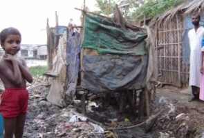 """Sanitation is horrendous throughout the community with use of """"hanging latrines."""" The human waste simply drops on the ground below the latrine and accumulated until it is washed away. Kazituri, Dhaka, Bangladesh. (Photo by Gary White/Water.org)"""