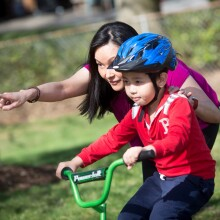 A photo of a mother teaching her son to ride a bicycle