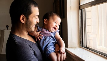 A father and baby look out the window
