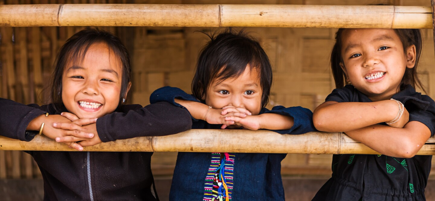 A photo of three girls smiling and resting their arms on a bamboo bar