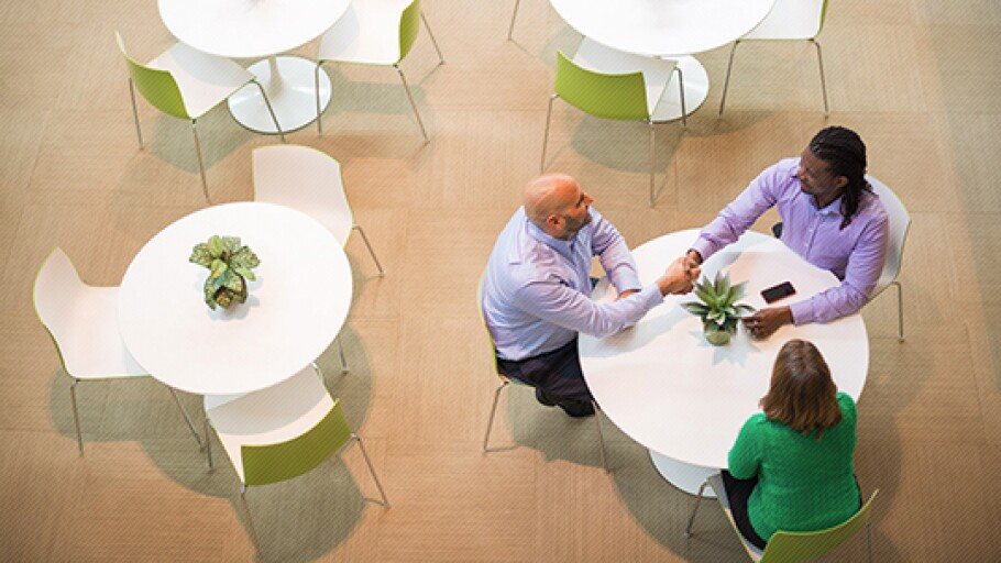 A photo of three people sitting at a table and shaking hands