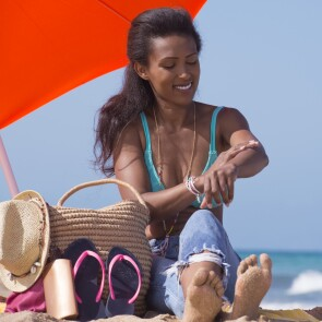 Woman sitting next to a beach bag, hat and flip-flops applying sunscreen to her arm