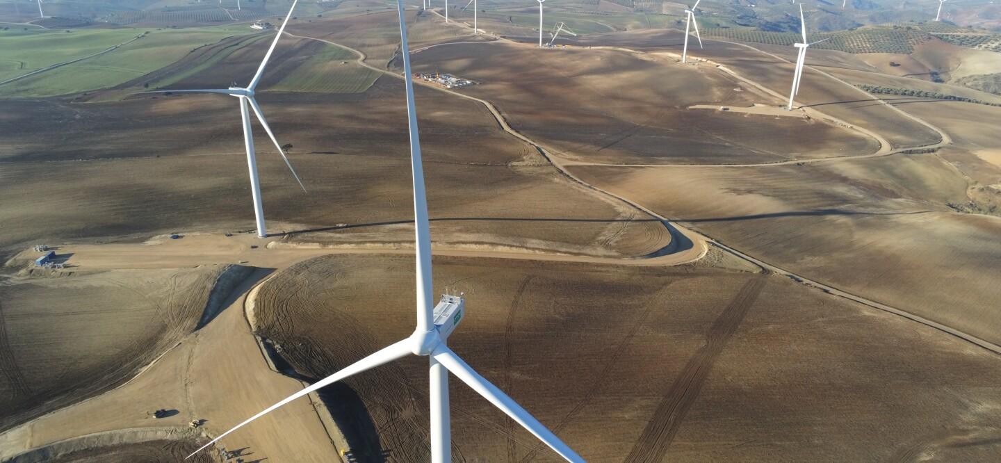 Aerial photograph of a wind farm in arid Spanish landscape with the sea beyond.