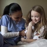 A nurse making a young patient smile