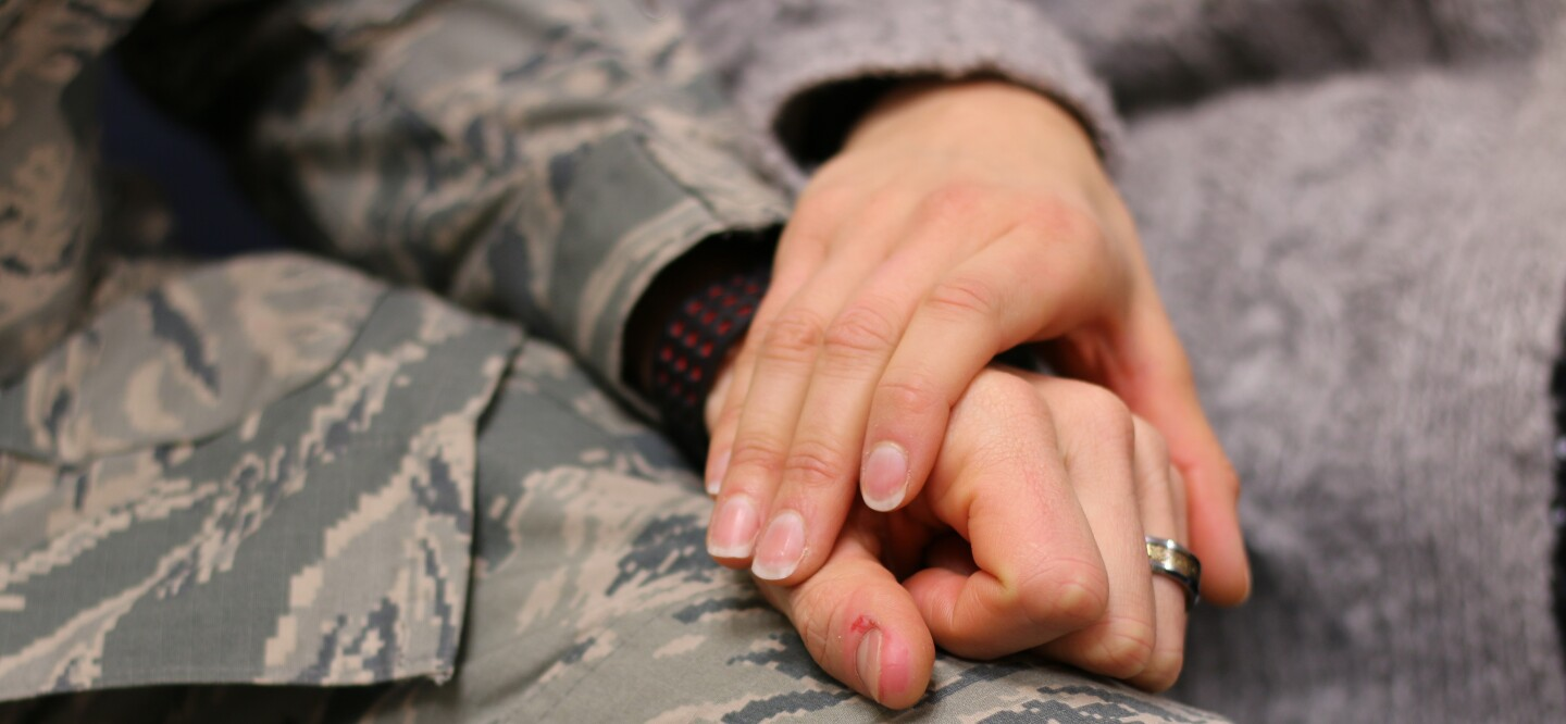 A photo of a military couple holding hands